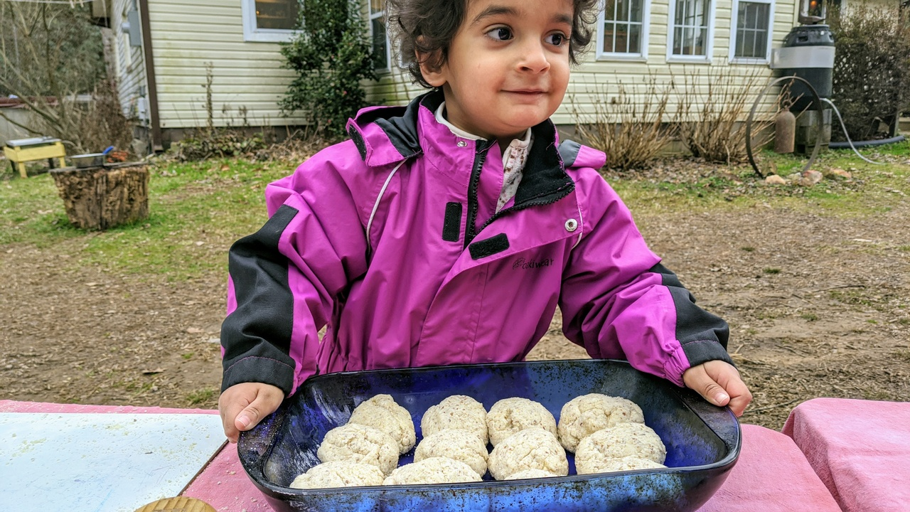 young child holding a baking pan filled with gluten free bread rolls. picture from Little Round Schoolhouse