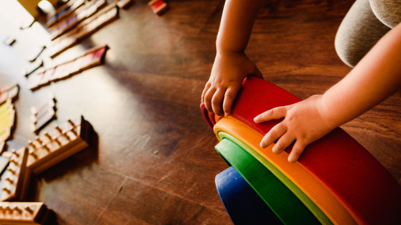 Child with wooden Waldorf rainbow stacker. Photo from Little Round Schoolhouse.