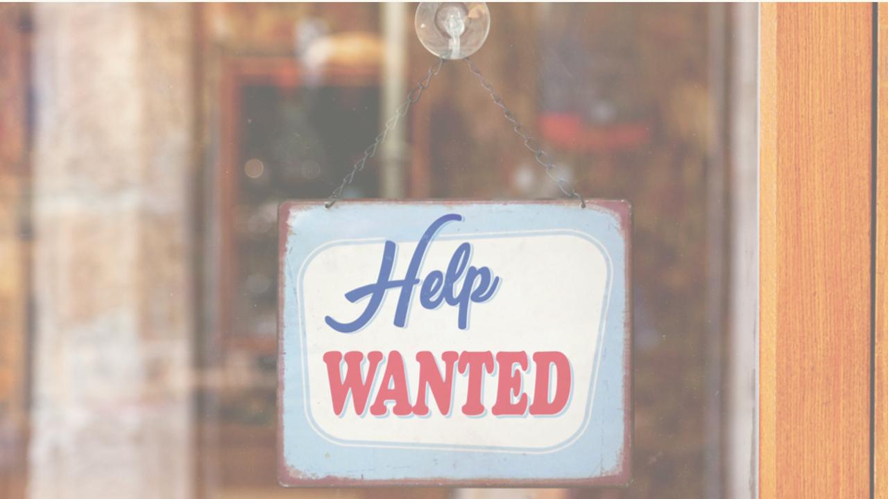 help wanted sign in window of retail store door
