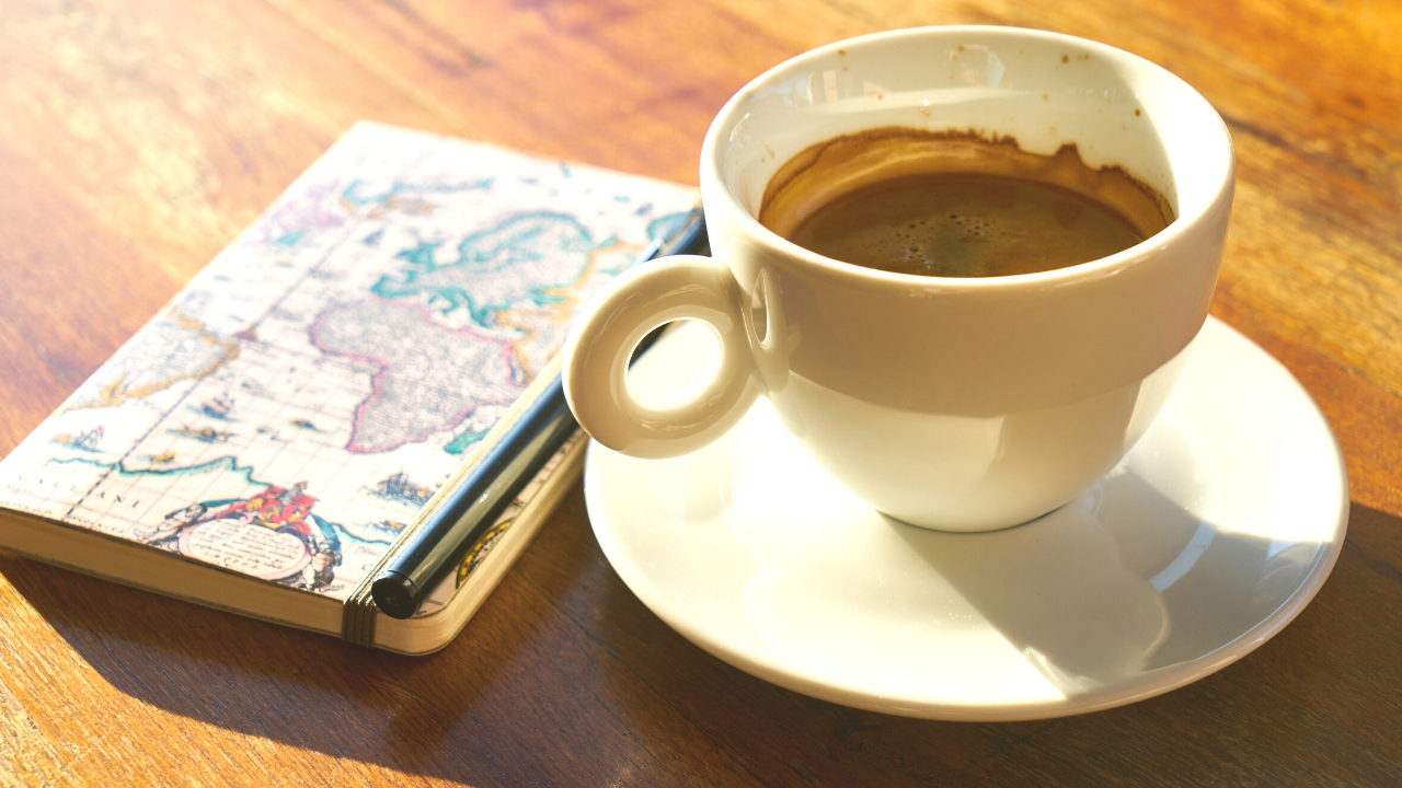 Coffee cup with journal on a desk.