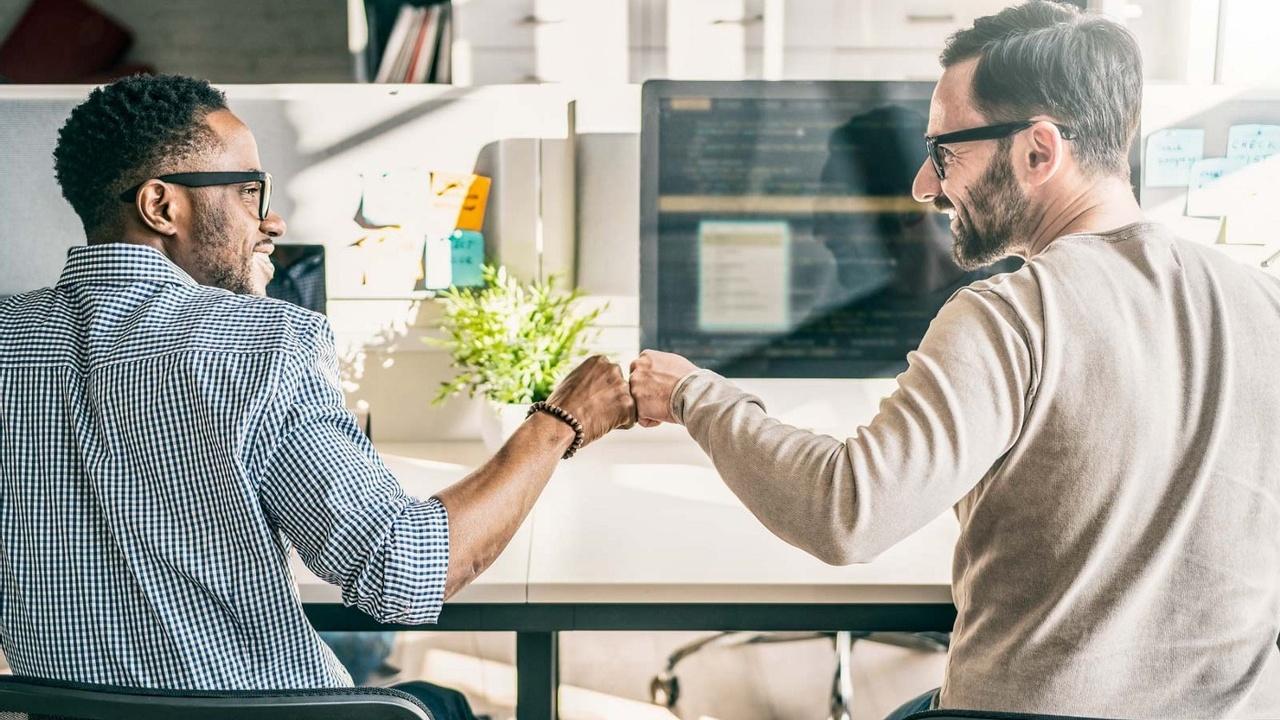 Two men in glasses fistbump at desk