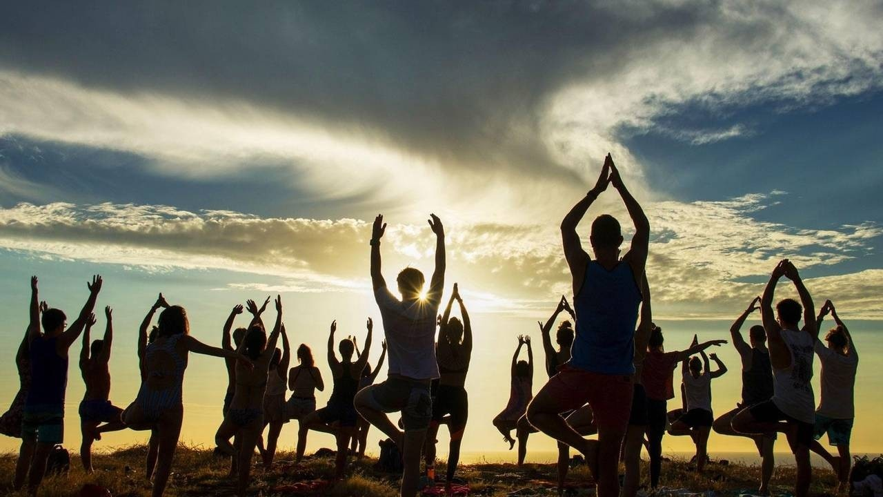 Silhouette of group practising yoga as the sun rises