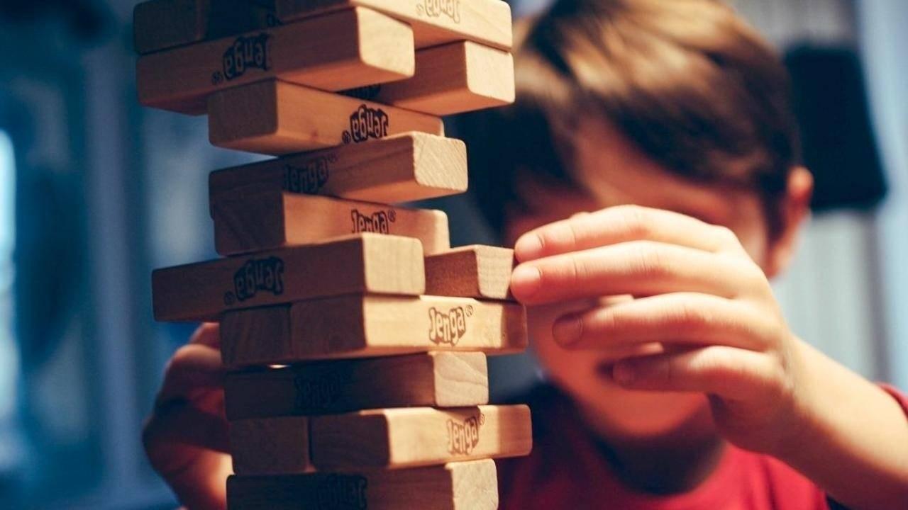 Boy rebuilding big jenga tower