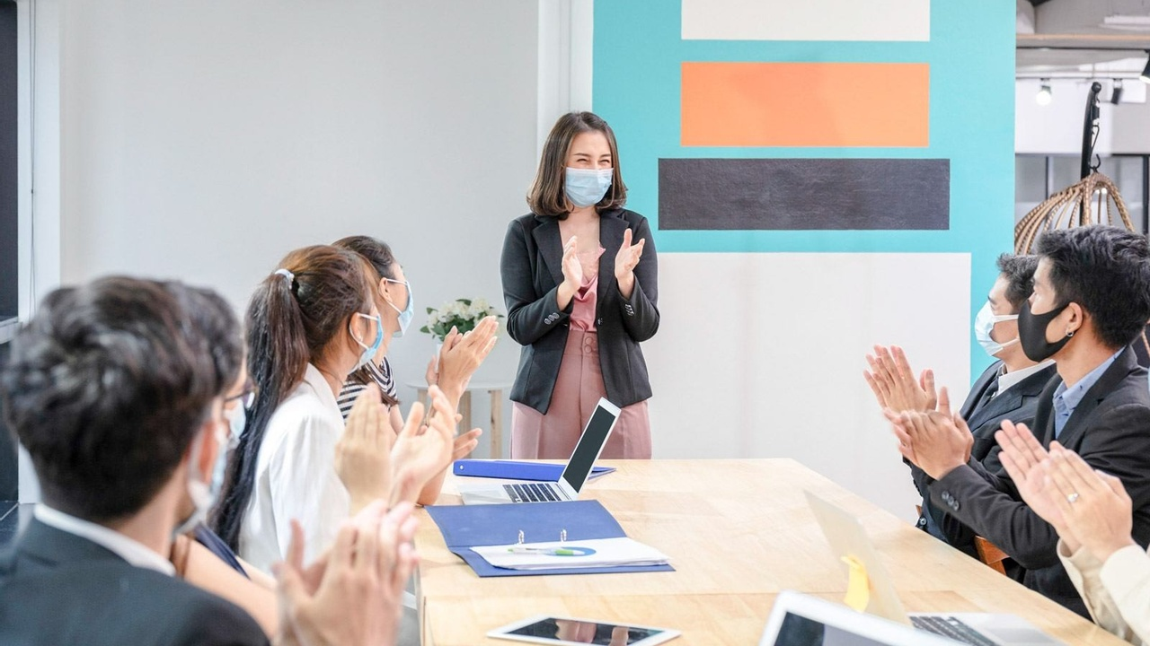 Women stands at head of management meeting in mask clapping