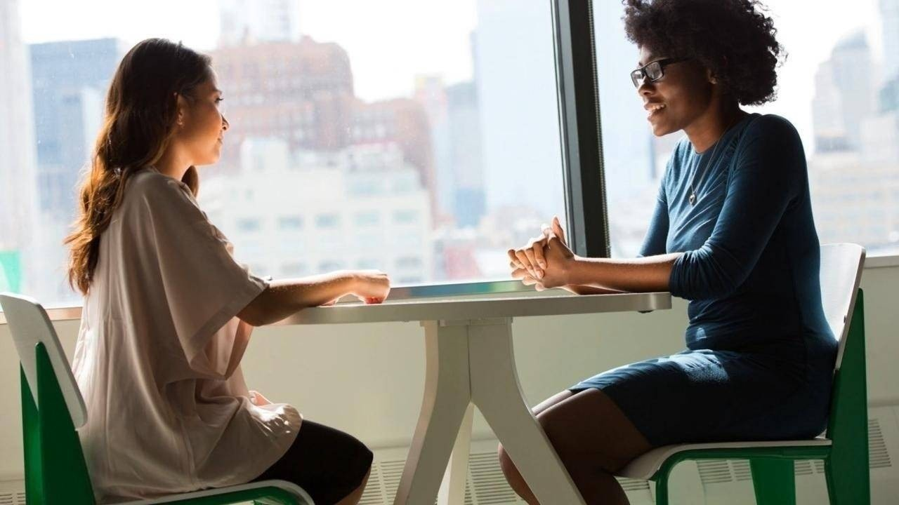 Two women sat at table in feedback meeting