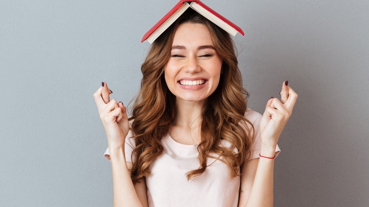Women crossing her fingers for luck with book balanced on her head