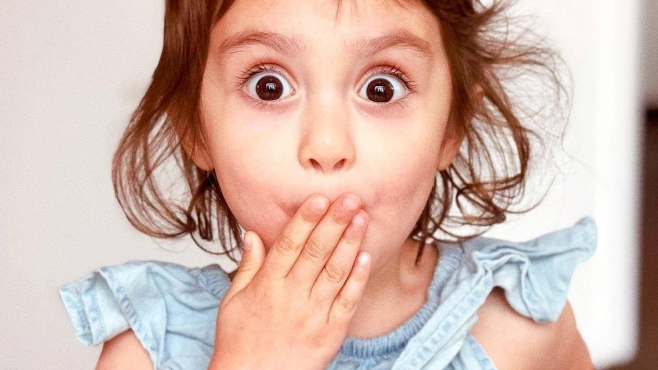 Girl with hand over mouth in surprise