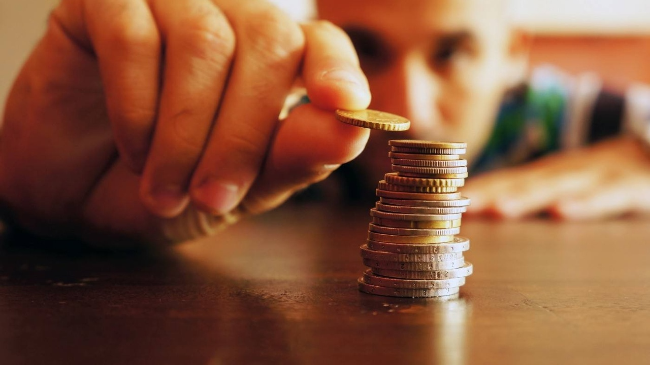 Man stacks coins on a table