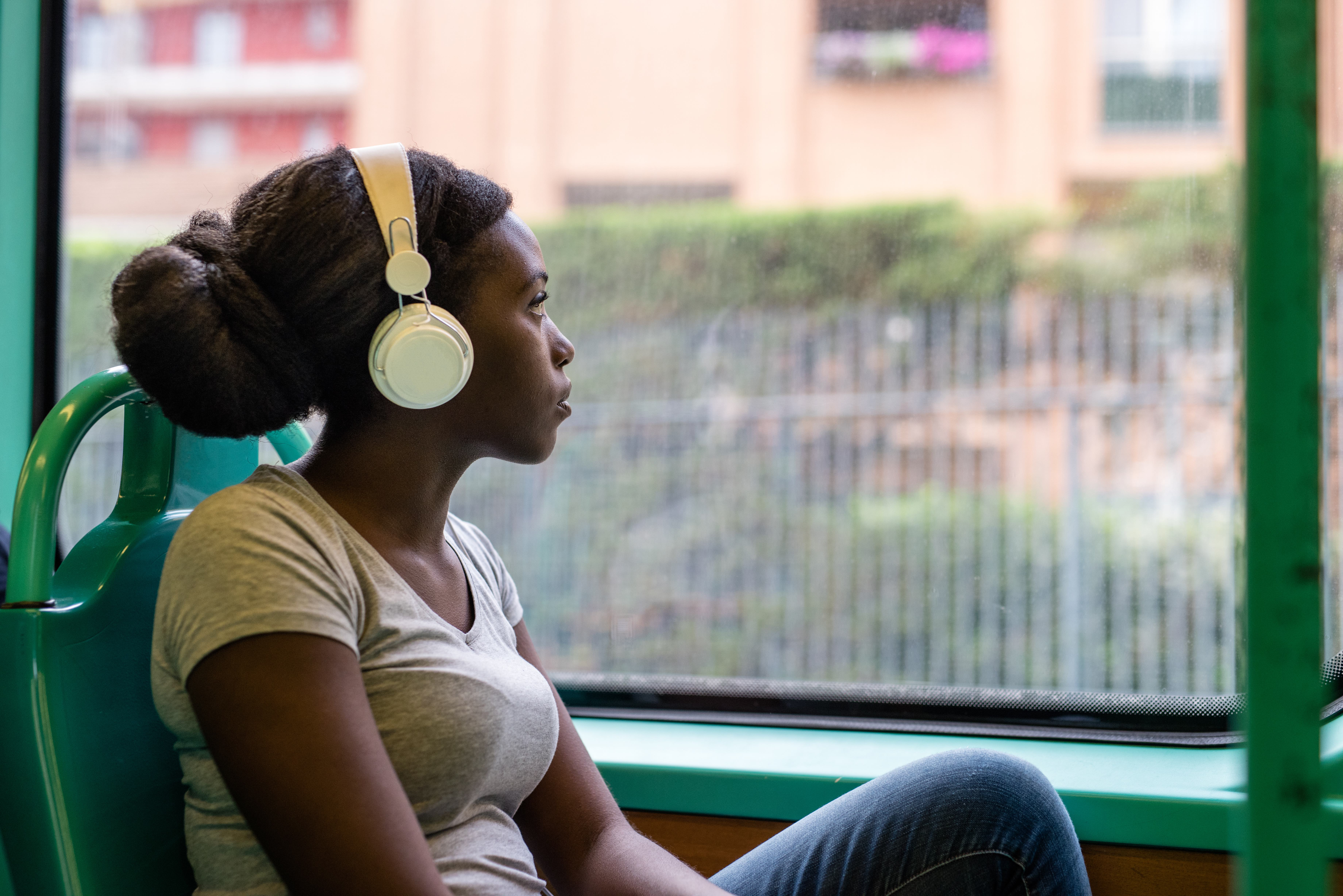 young Black girl on bus with headphones on looking out window