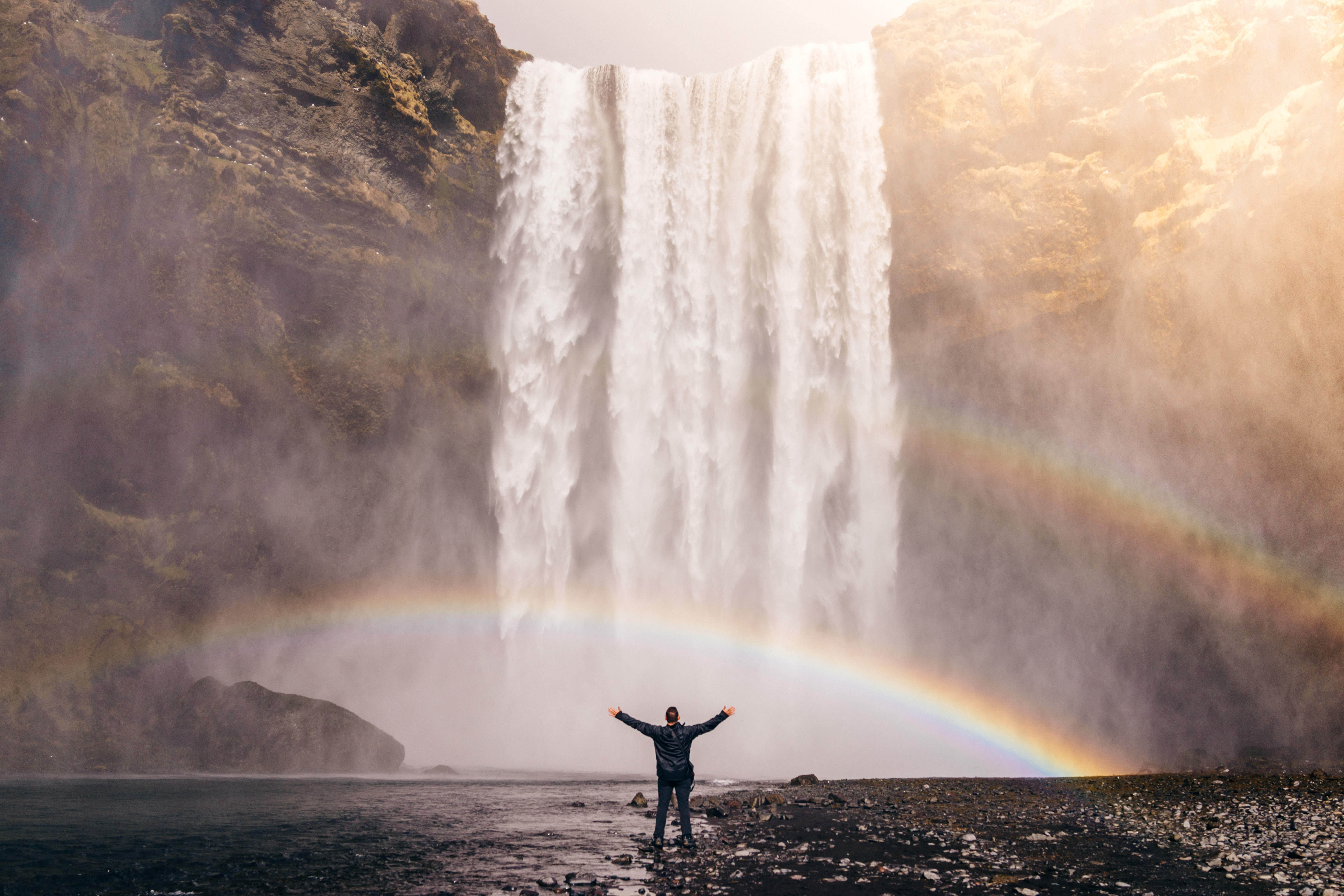 man standing in front of rushing waterfall