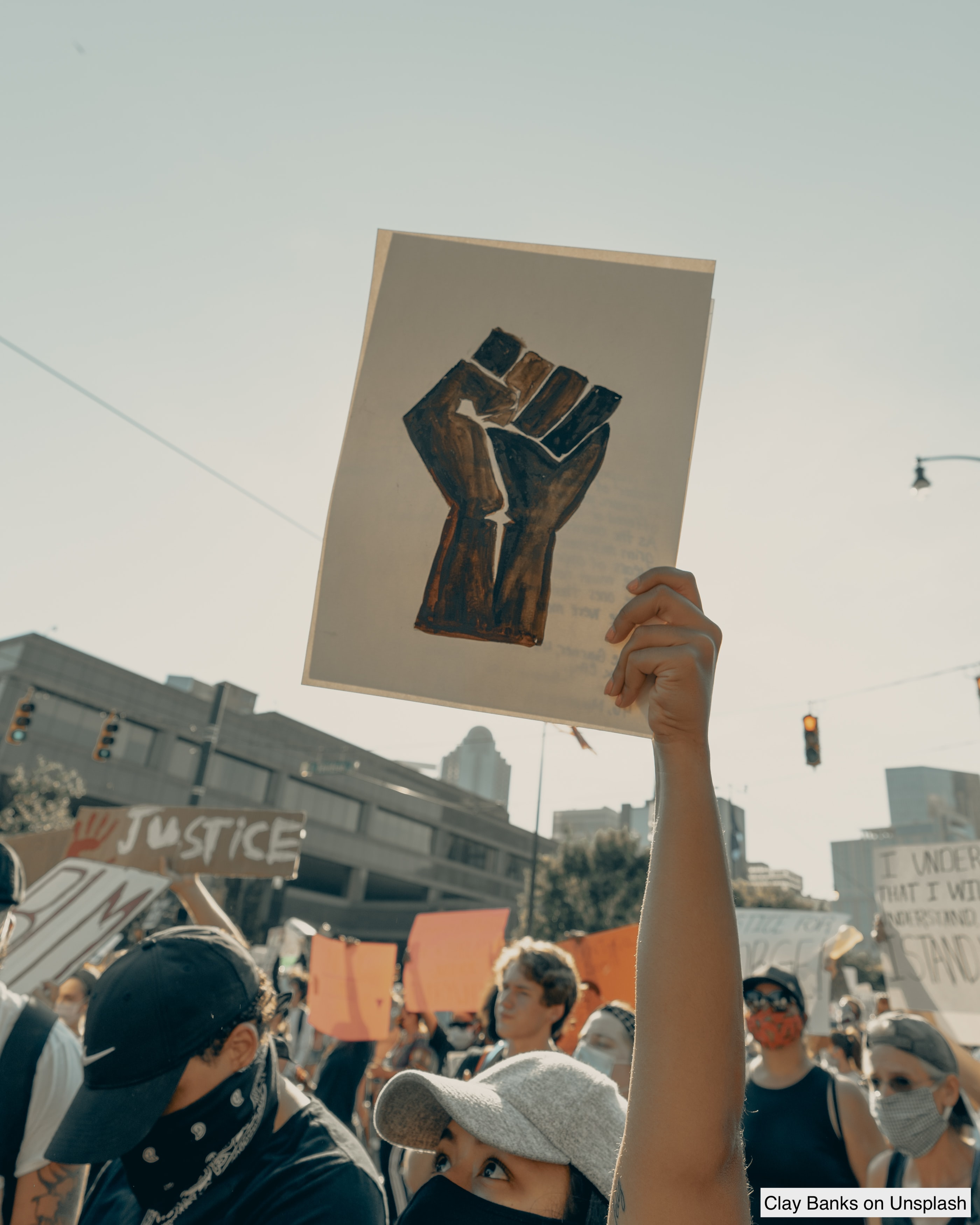protestor holding sign with a drawing of a black fist