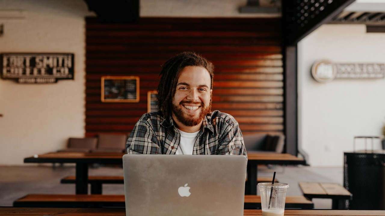 Man sitting in front of a laptop smiling.