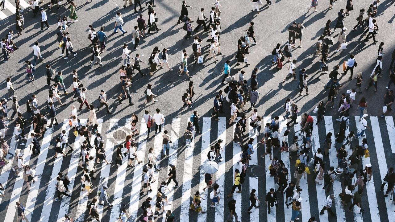 Many people walking across a road.