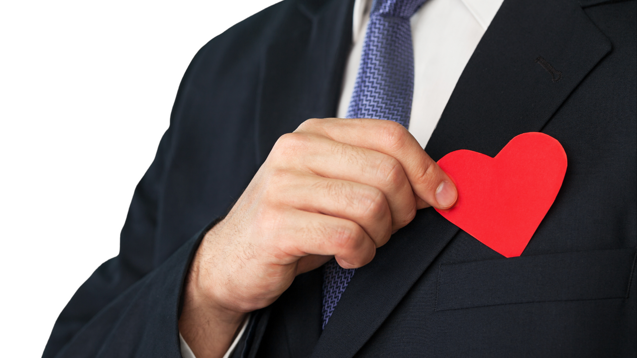 This image shows a leader putting a paper cut heart on his pocket. This somehow illustrates that EQ is important in leadership