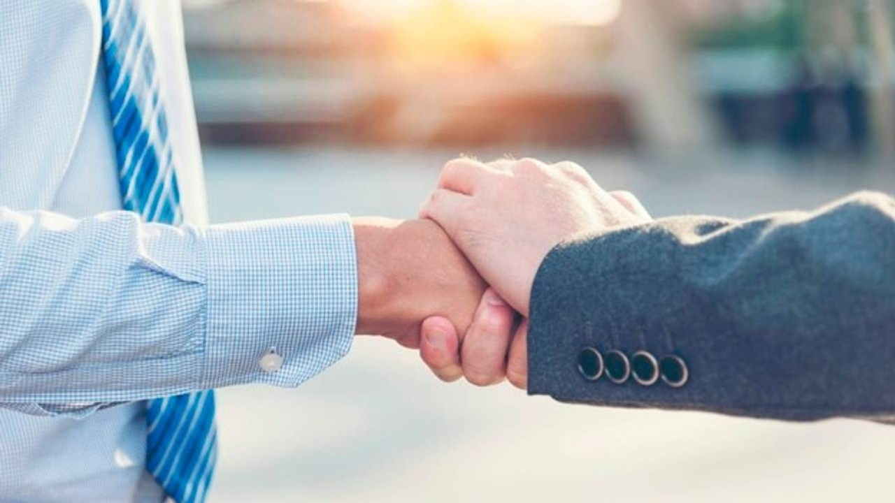 Leader and employee shaking hands as a sign of trust.