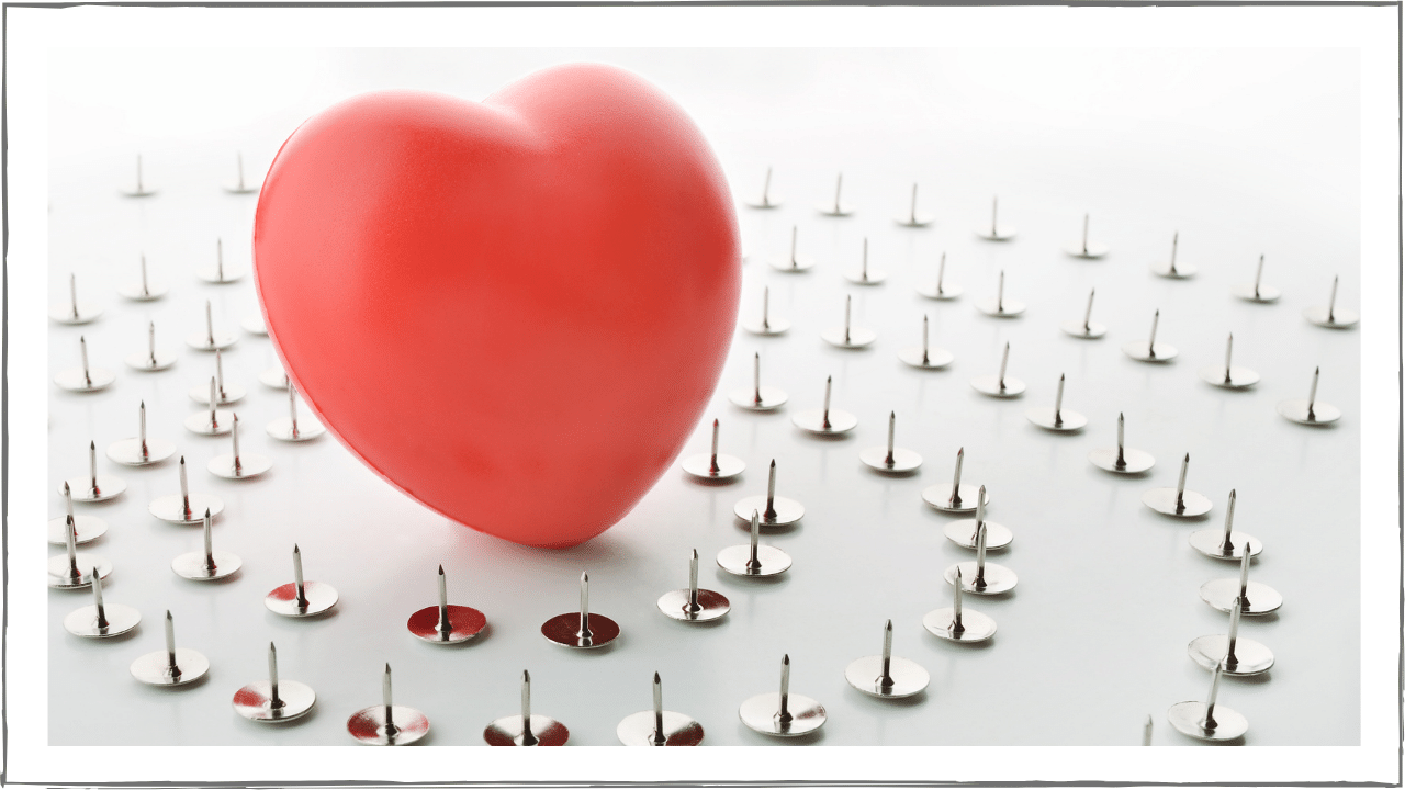 Heart-shaped balloon surrounded by concentric circles of up-turned tacks.