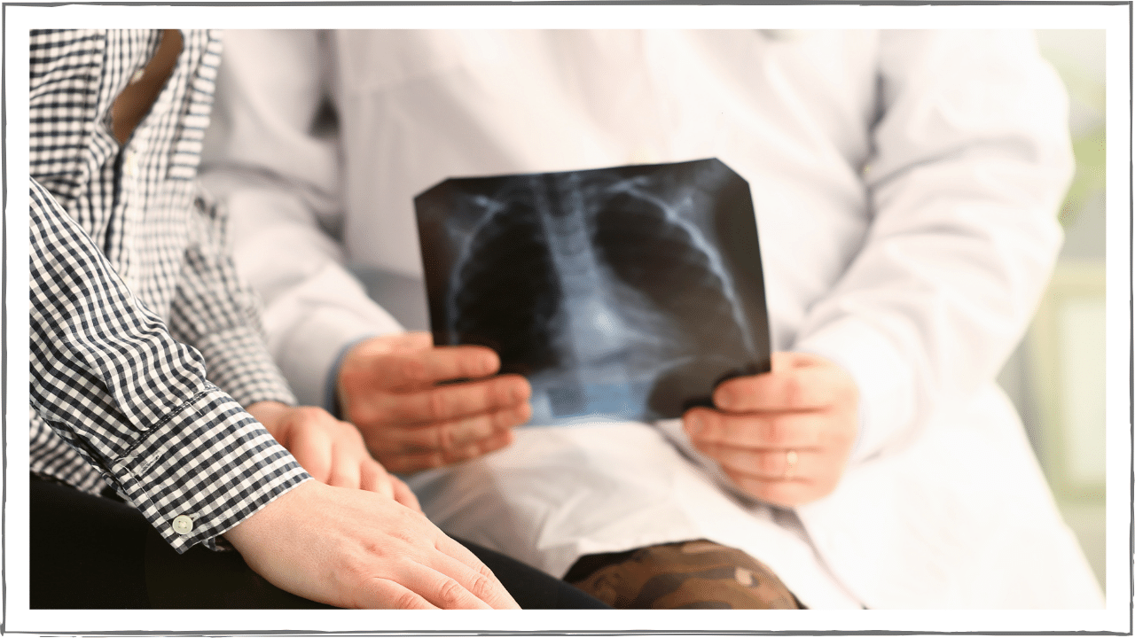 Doctor sitting with patient holding a copy of chest x-ray