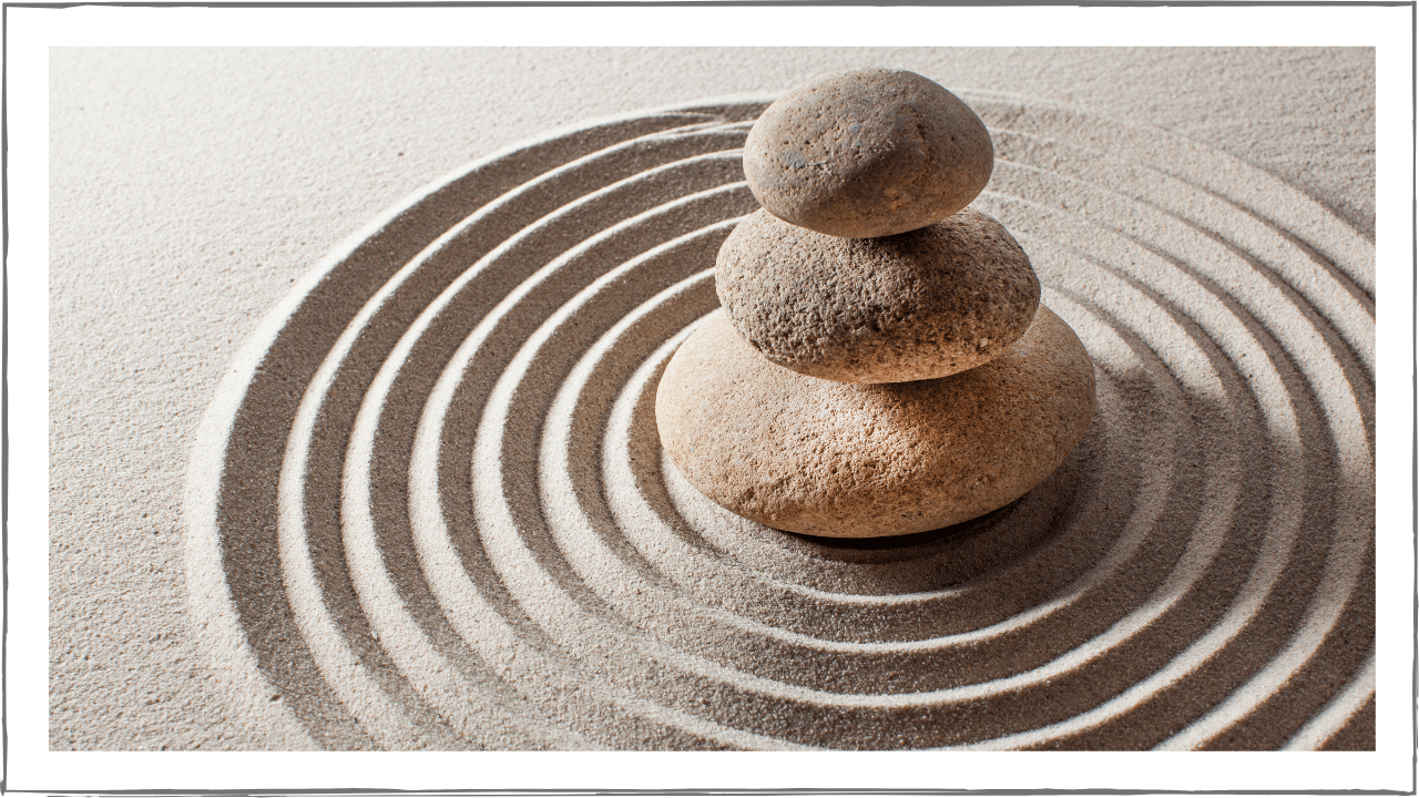Three stones stacked with sand raked in circles leading to the pile.