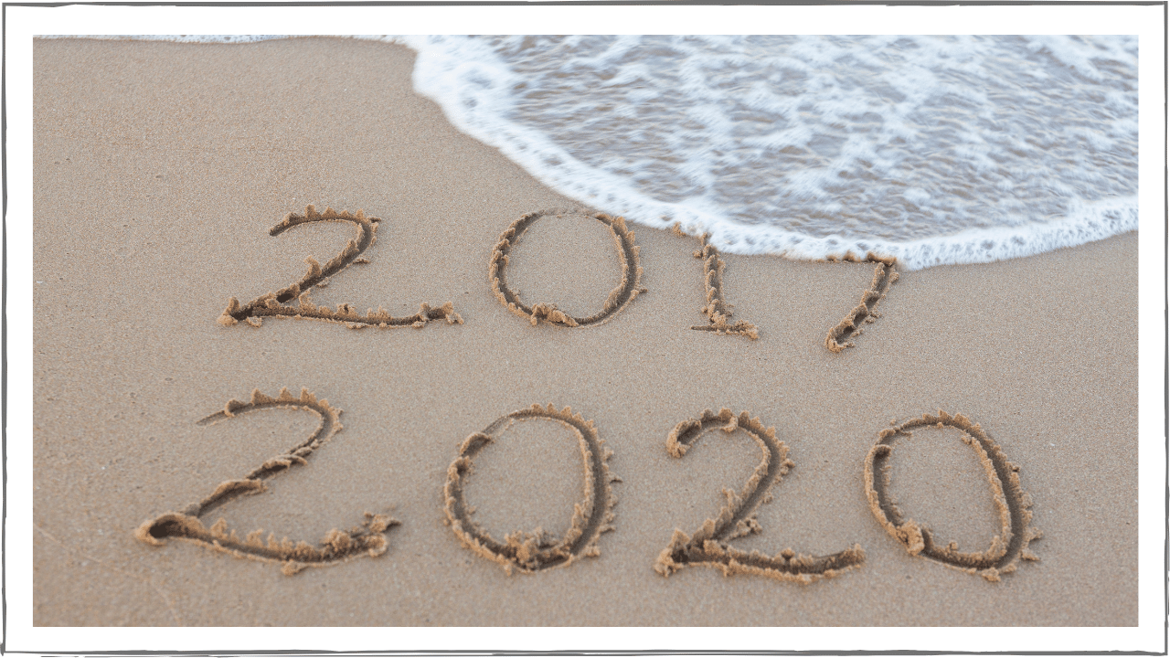 2019 and 2020 written in the sand. Wave washing 2019 away.