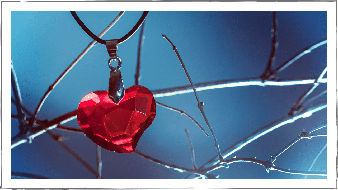 Glass heart hanging in barren winter tree branches.