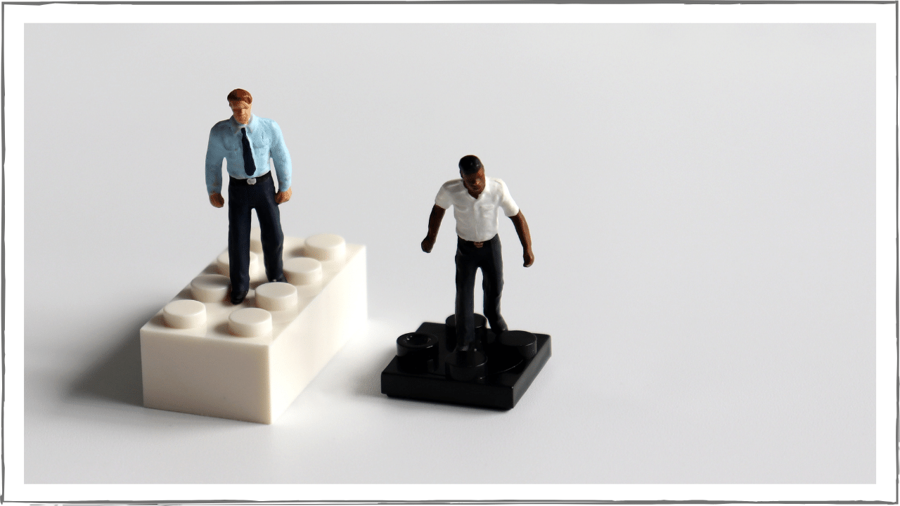 Two people standing on Legos, one white, one black.  The white person's Lego is much taller and further ahead.  The black person's Lego is almost flat and further behind.
