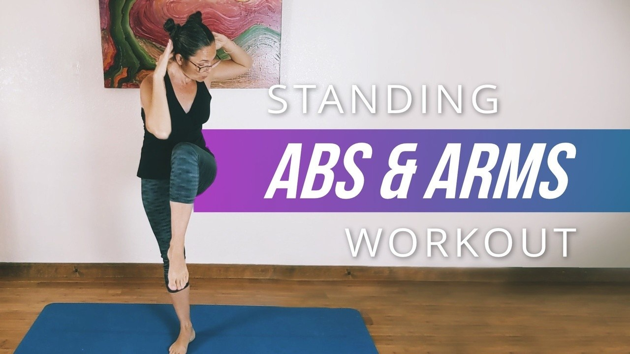 picture of a woman doing a standing Pilates abdominal exercise. She's standing on her mat and lifting one leg while curling her upper body towards her lifted leg.