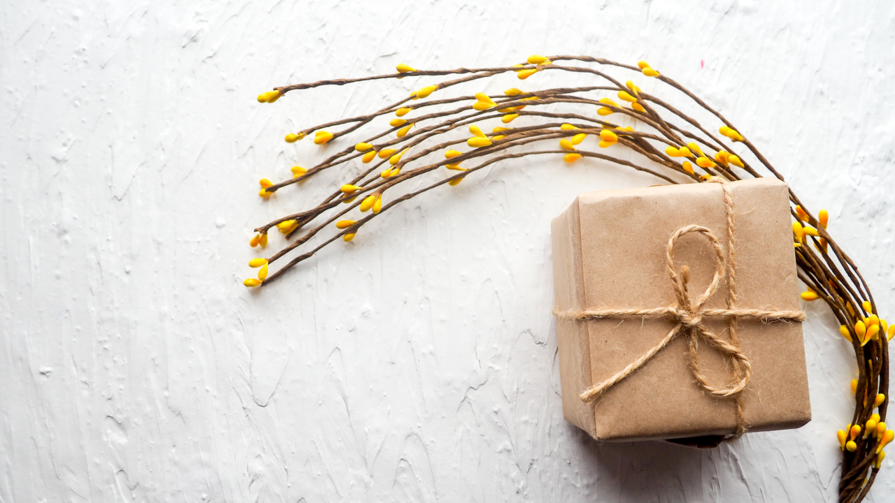 brown paper package with forsythia stems and blooms