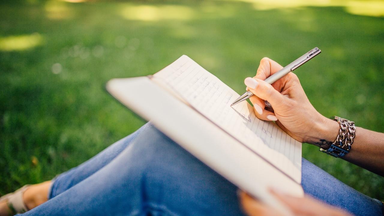 Kvinna sitter utomhus och skriver.