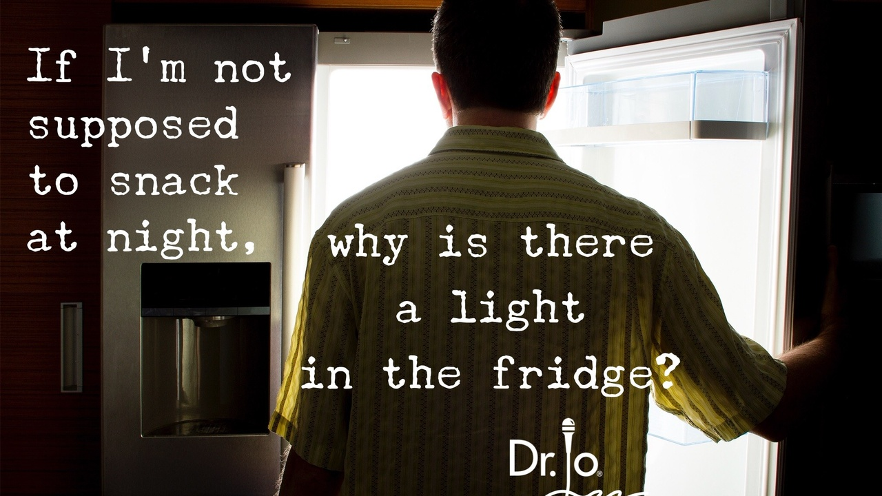 man looking for food in refrigerator at night