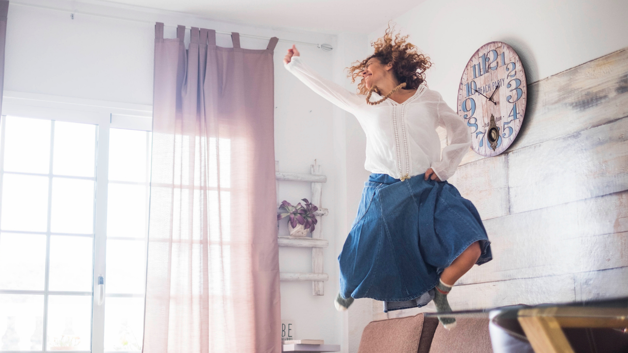 woman at home jumping for joy
