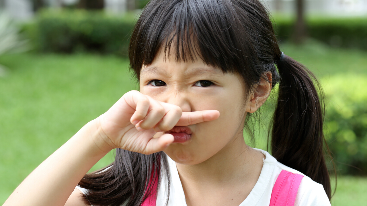 A girl holding her finger up to her nose smelling in disgust