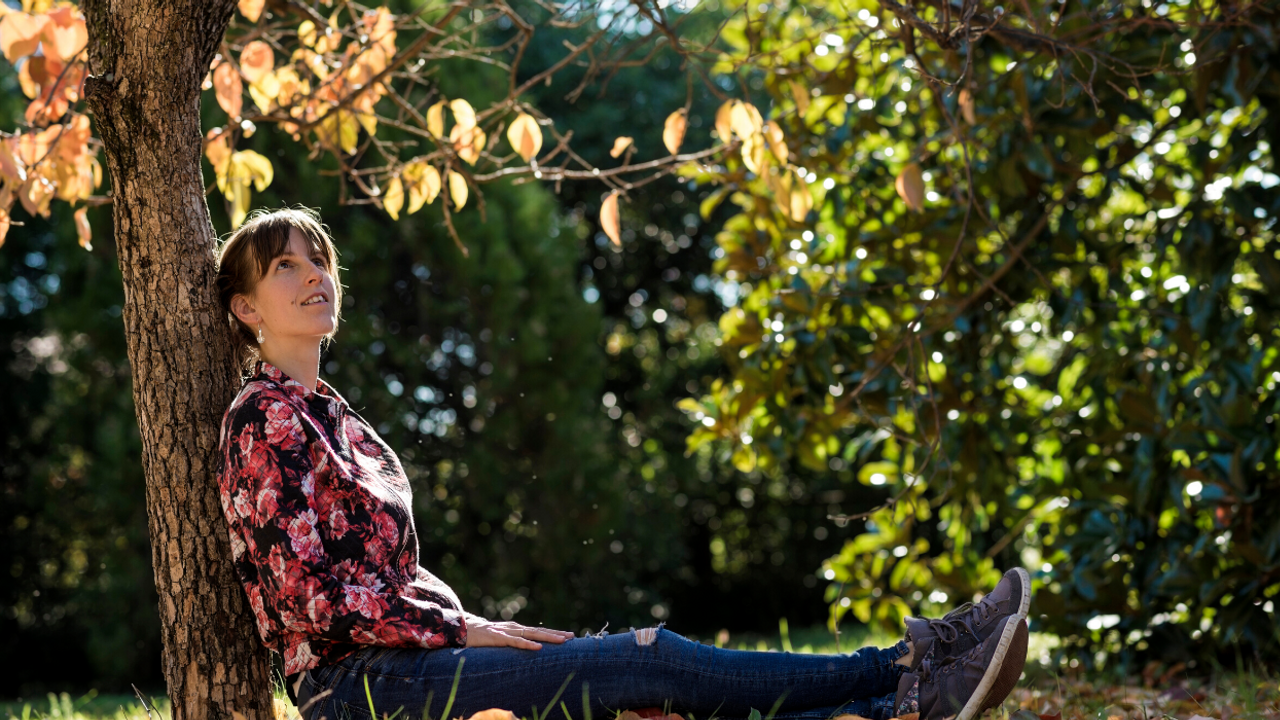 Woman sitting under a tree looking up at the leaves
