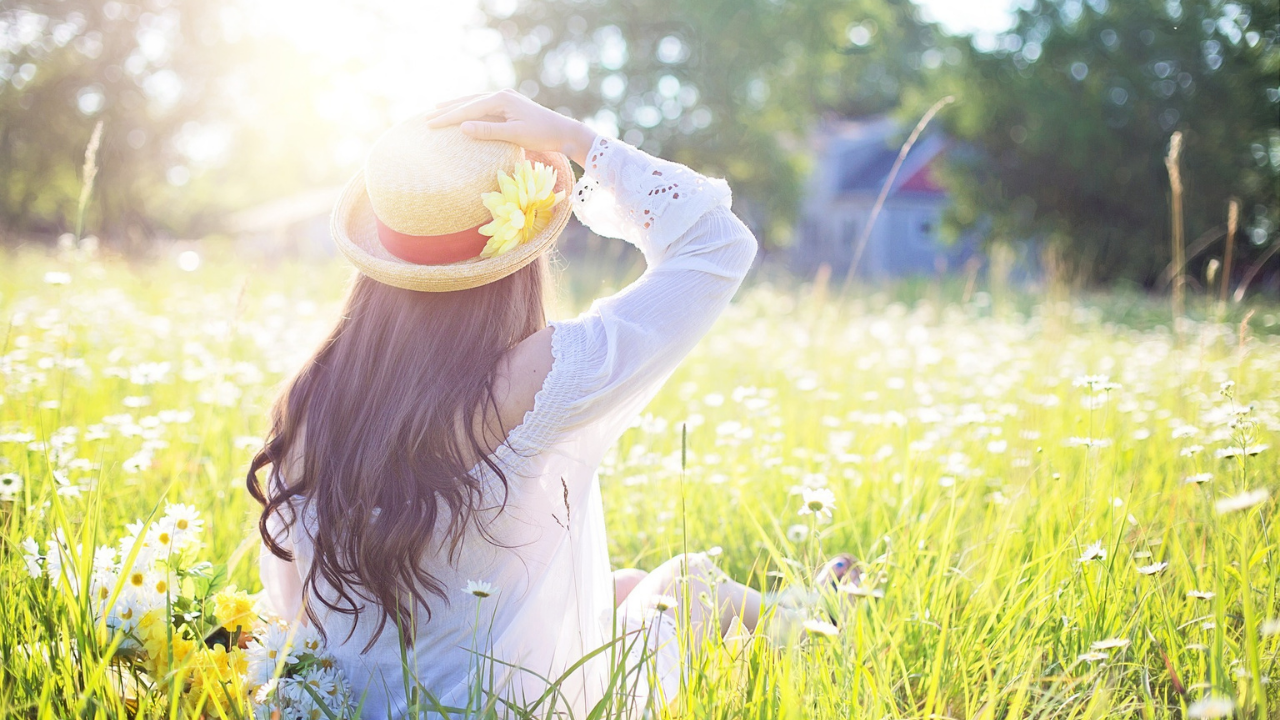 A woman holding her hat sitting in a field of flowers. Phototoxic essential oils blog post.