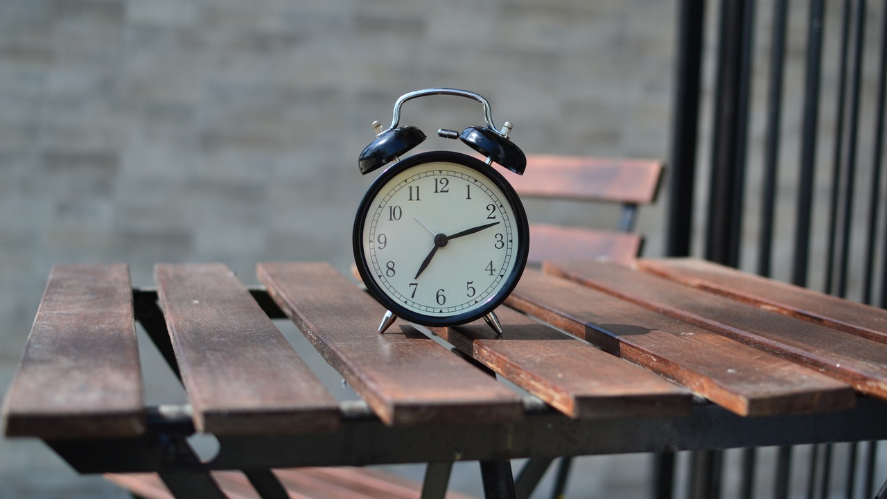 a clock standing on a picnic table