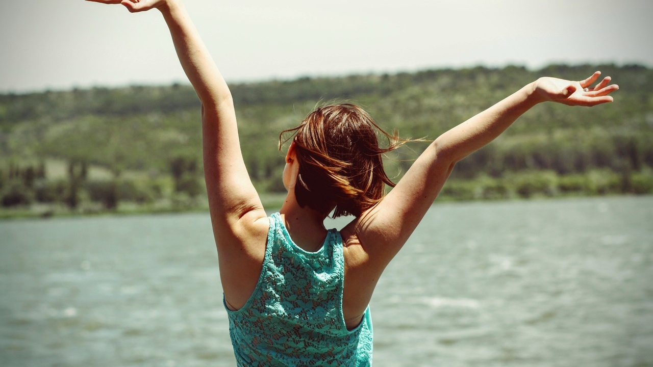 a woman at a lake raising her arms in joy