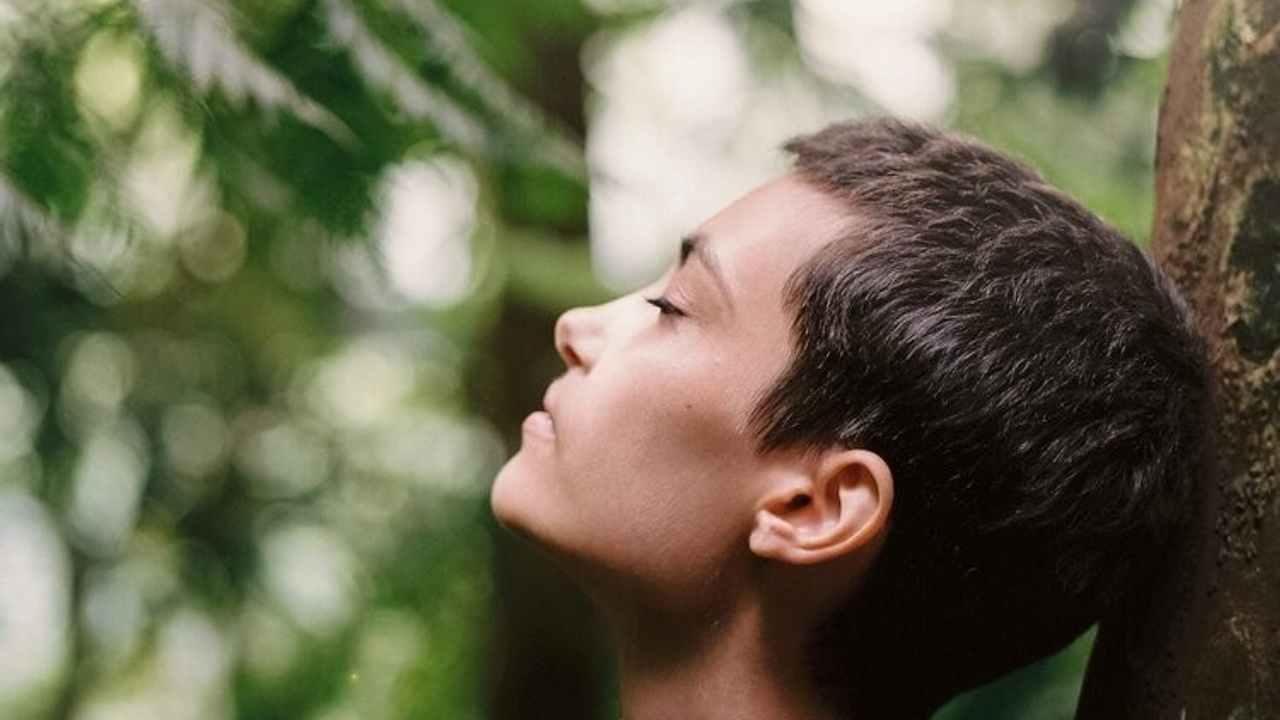 A woman leaning against a tree with her eyes closed