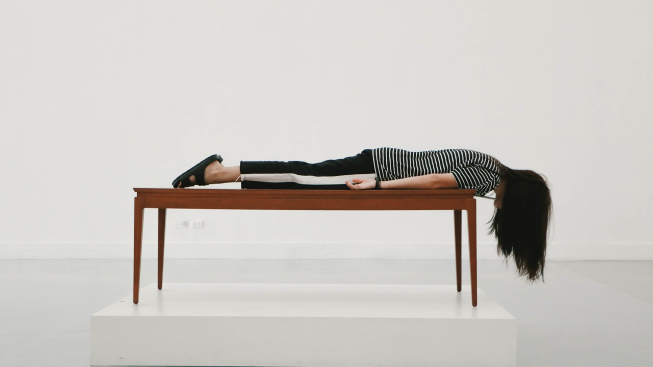 a woman lying on top of a table hanging over the edge with her hair draping down, looking tired