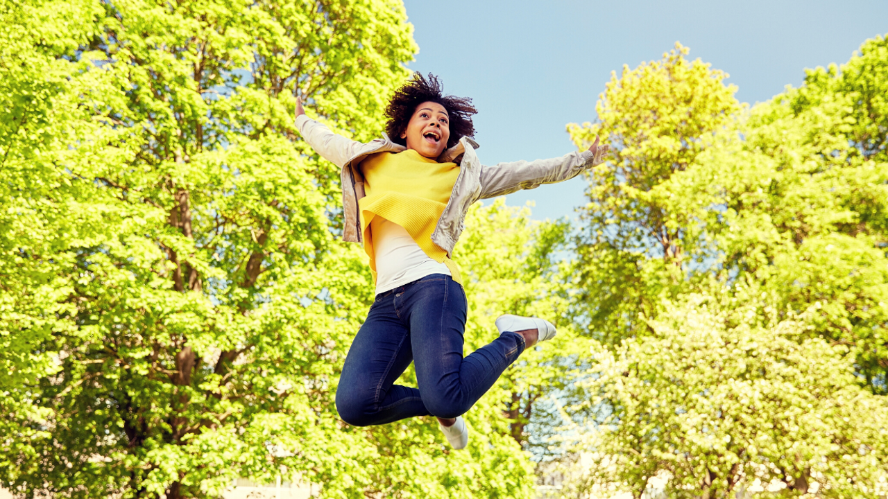 A woman jumping up in the air happy with yellow-leaved trees in the background