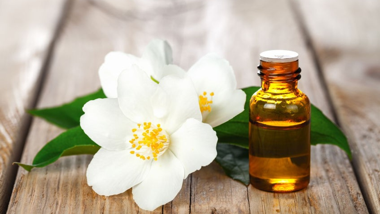 An essential oil bottle next to a white flower on a wooden table
