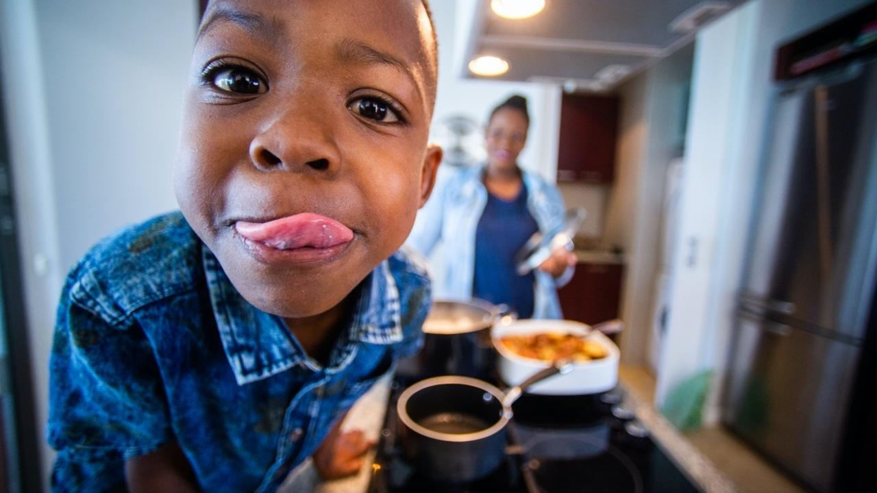 boy helping to cook foods with his family