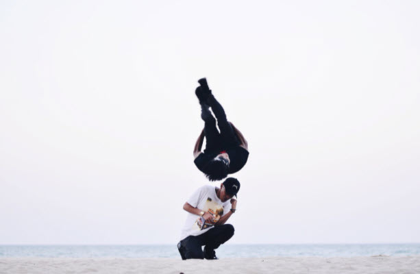A man practices flips on the beach
