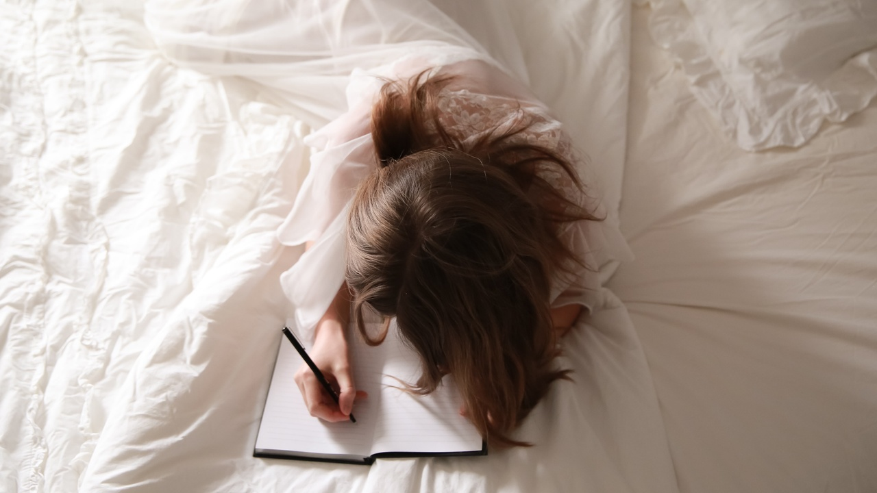 Woman laying on a bed with white sheets writing in a journal