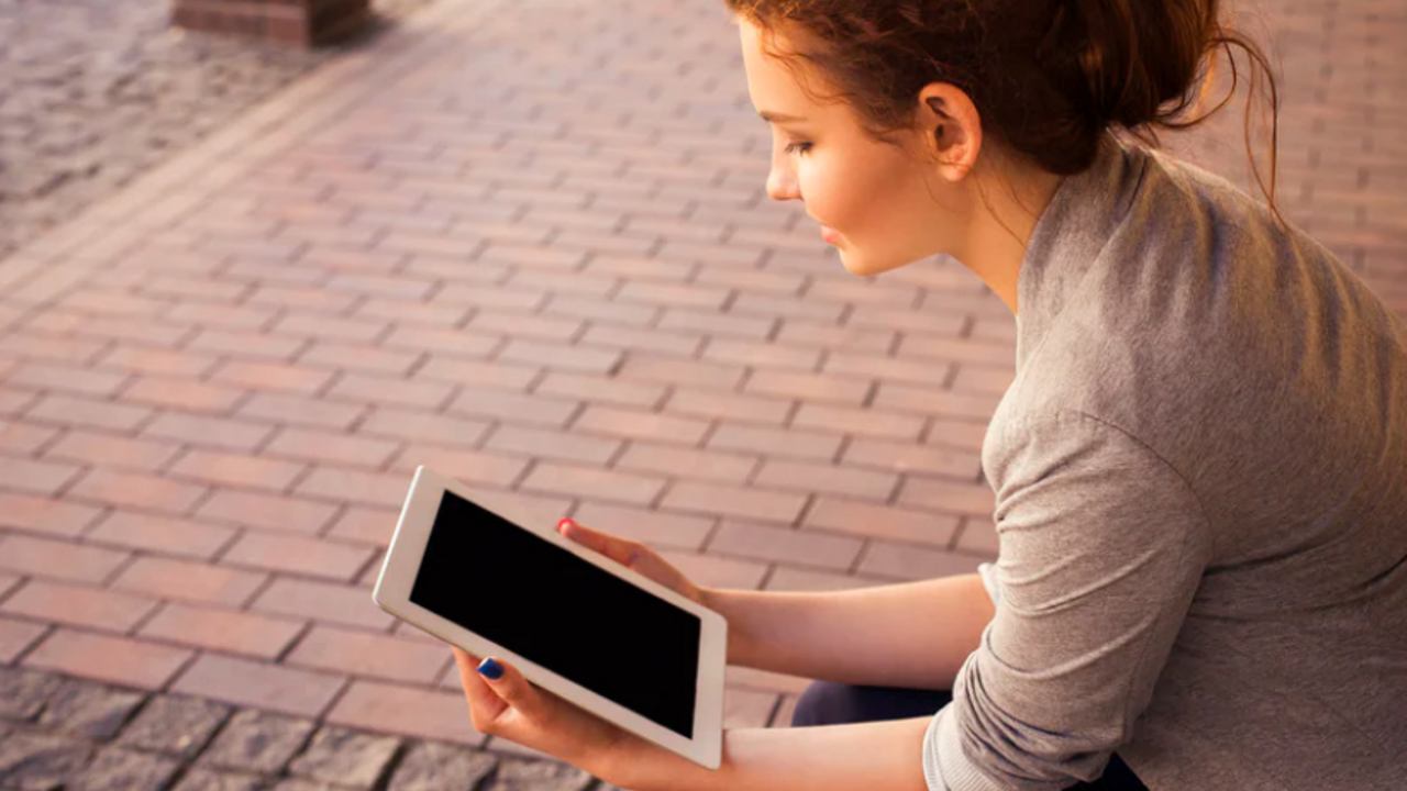 woman reading ipad, woman outdoors on tablet