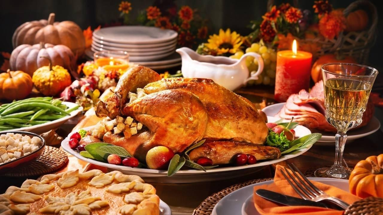 table overwhelmed with thanksgiving turkey and food