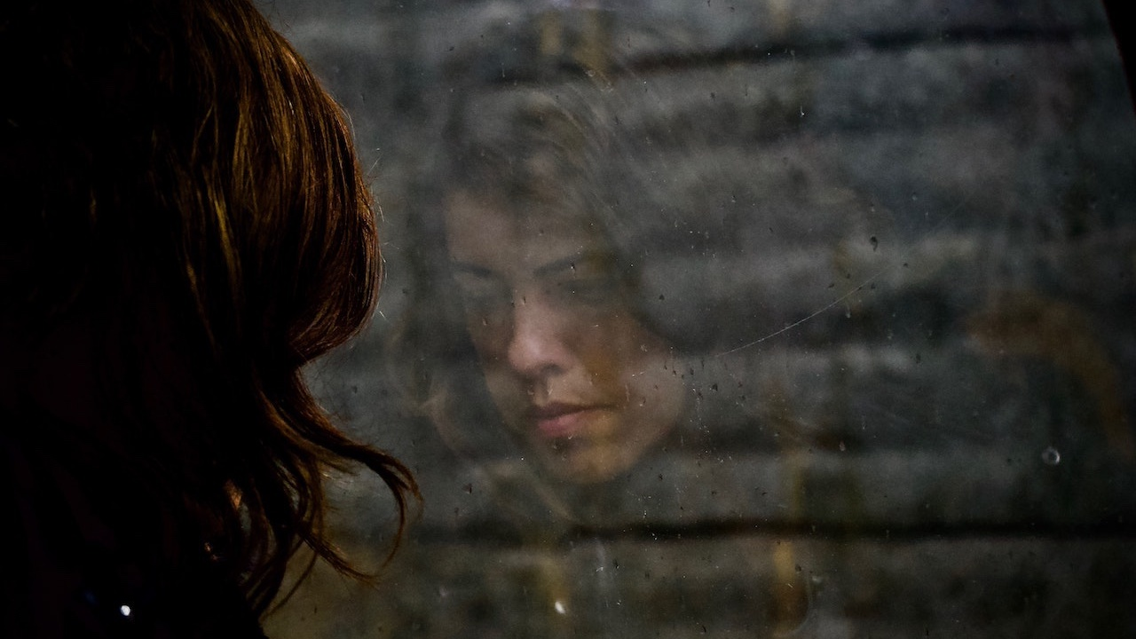 Reflection of depressed woman in the window