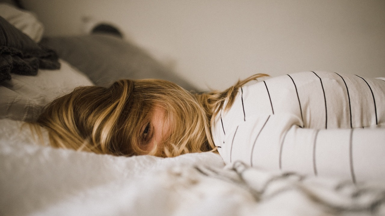Woman lying on bed with hair covering her face