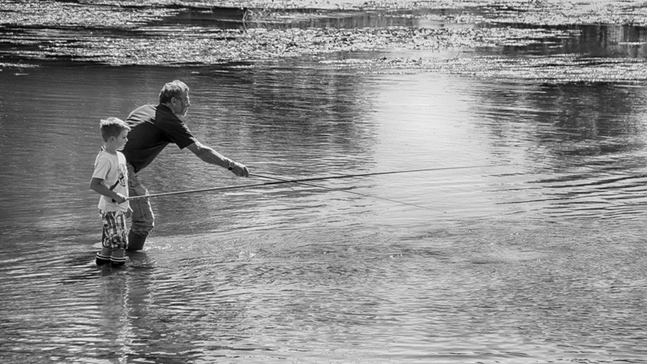 Father and son fly fishing in a river
