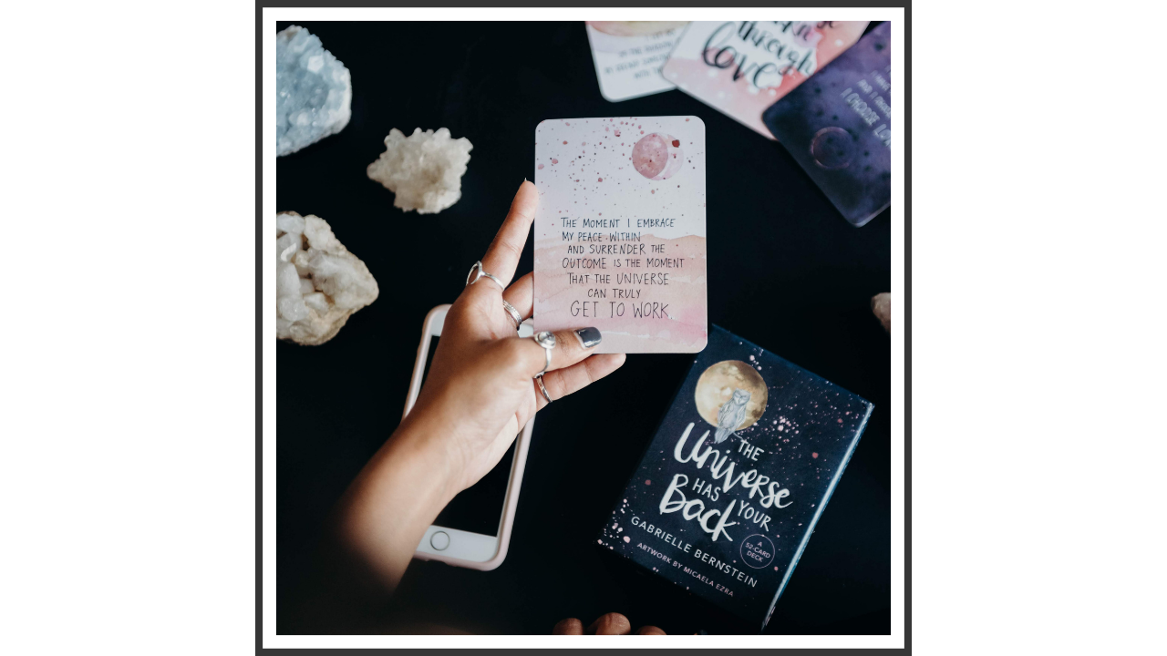 A woman's hand holding a tarot card, surrounded by a iPhone, card decks, crystals, and a yoga mat