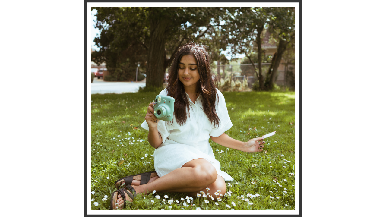 A girl in a white dress, holding a polaroid camera, sitting in a grassy park.