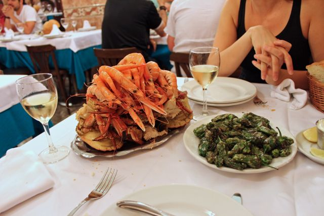 A seafood platter and pimientos de Padrón on a table at Ribeira do Miño, Madrid seafood restaurant